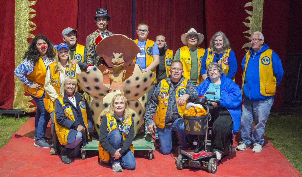 Several Bayside Lions Club members pose with the circus ring master and a dinosaur egg.